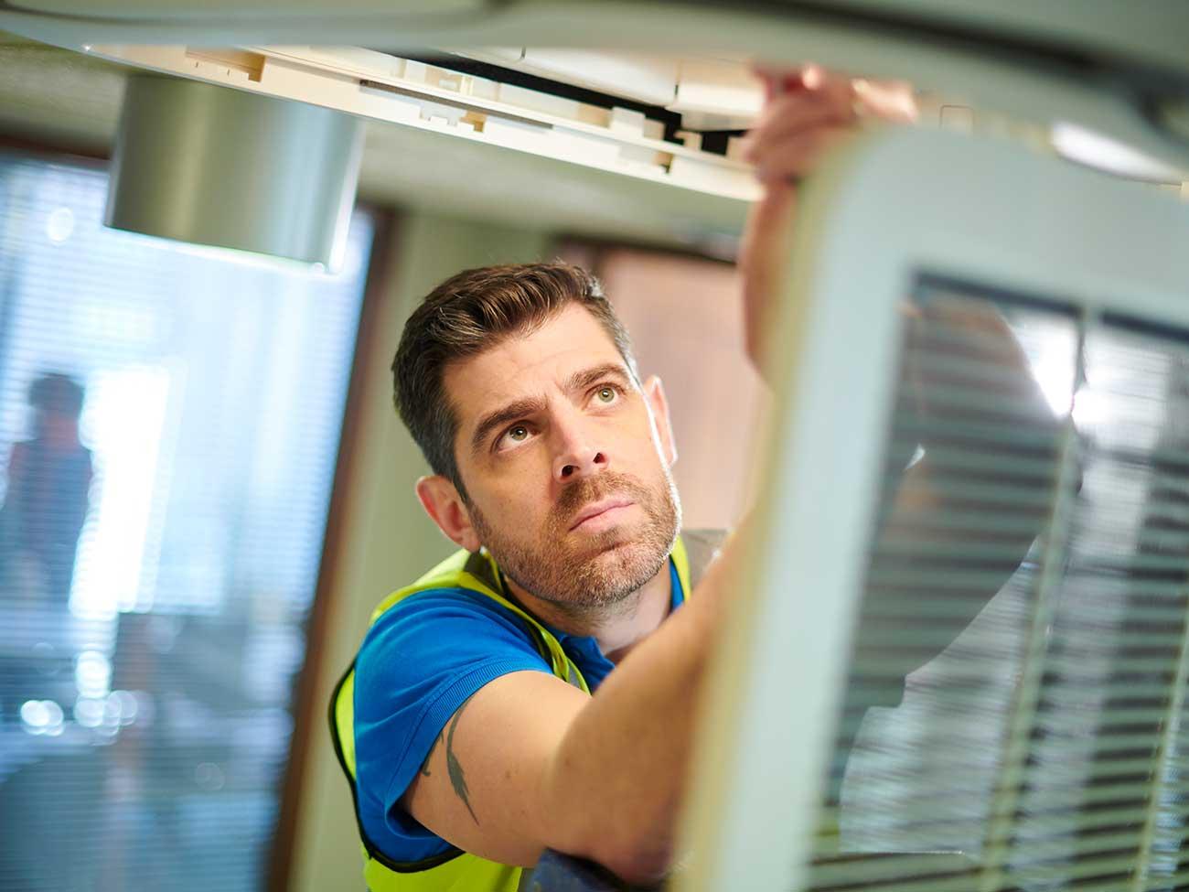 KLimatechniker arbeitet an Klimaanlage
