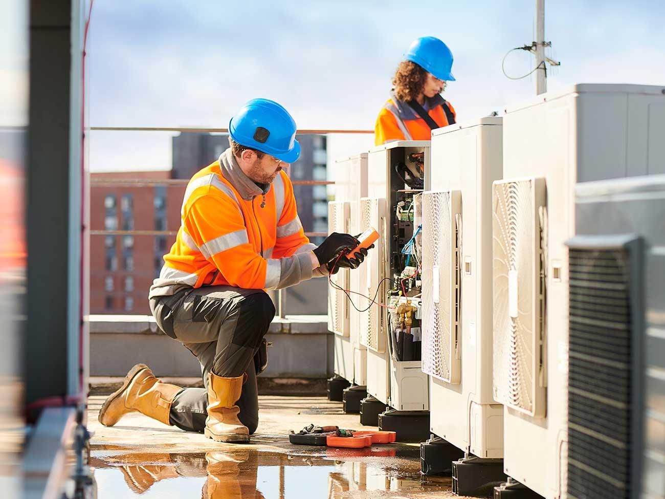 Zwei Klimatechniker arbeiten auf dem Dach
